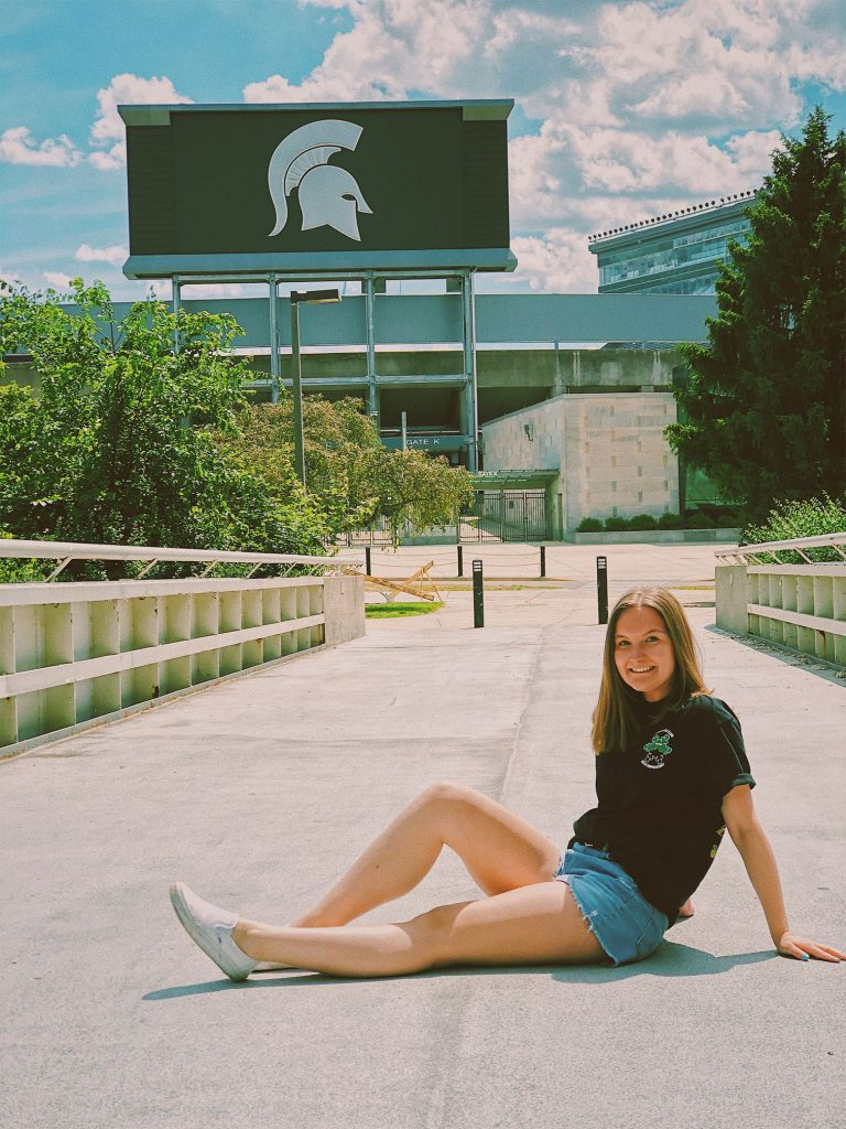 a girl in jeans and a green shirt sitting in front of the MSU football stadium