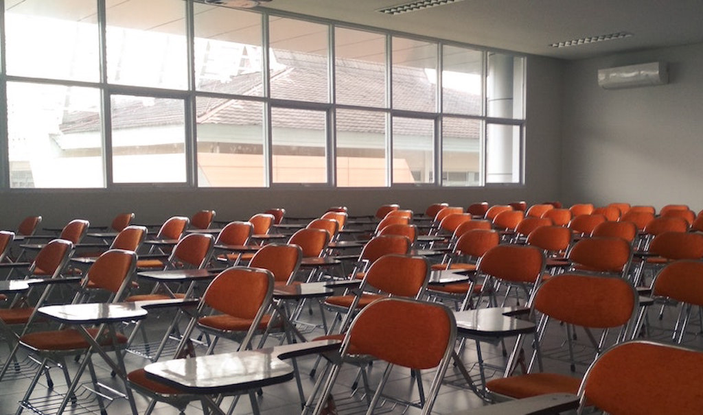 an empty classroom with desk chairs