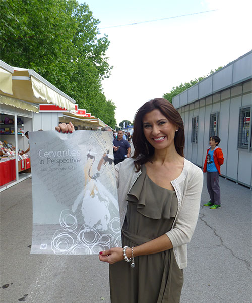 a woman with long brown hair wearing an olive colored dress holding a poster of a book cover