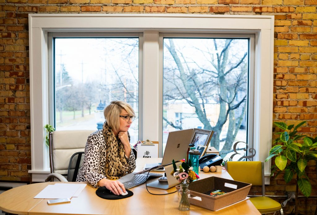 a woman with short blonde hair wearing a cheetah print shirt working in an office