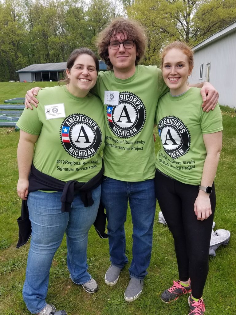 three people standing side by side wearing a green t shirt