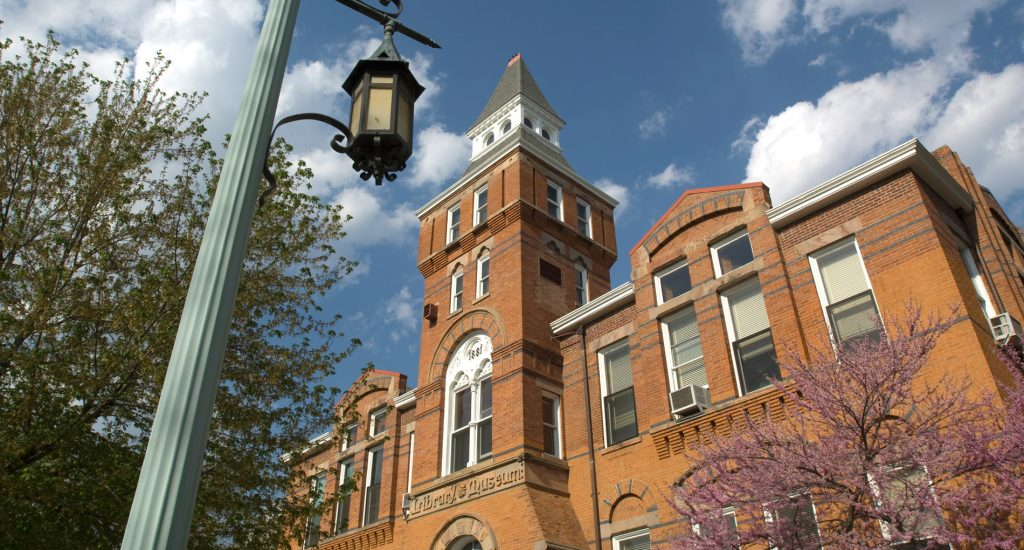 photo of an orange brick building with a clock tower in front of a cloudy sky and green trees as well as a light blue lantern lamppost to the left