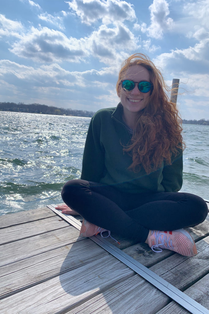 Hannah Kahn in sunglasses sitting on a dock next to the water.
