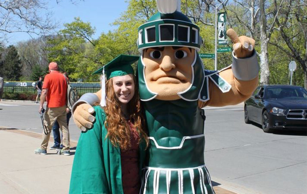 Woman in a green cap and gown standing outside next to Sparty