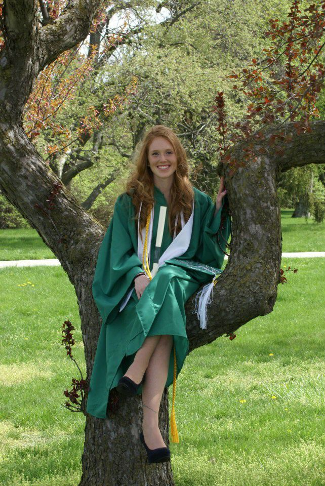 woman wearing a green gown sitting in a tree