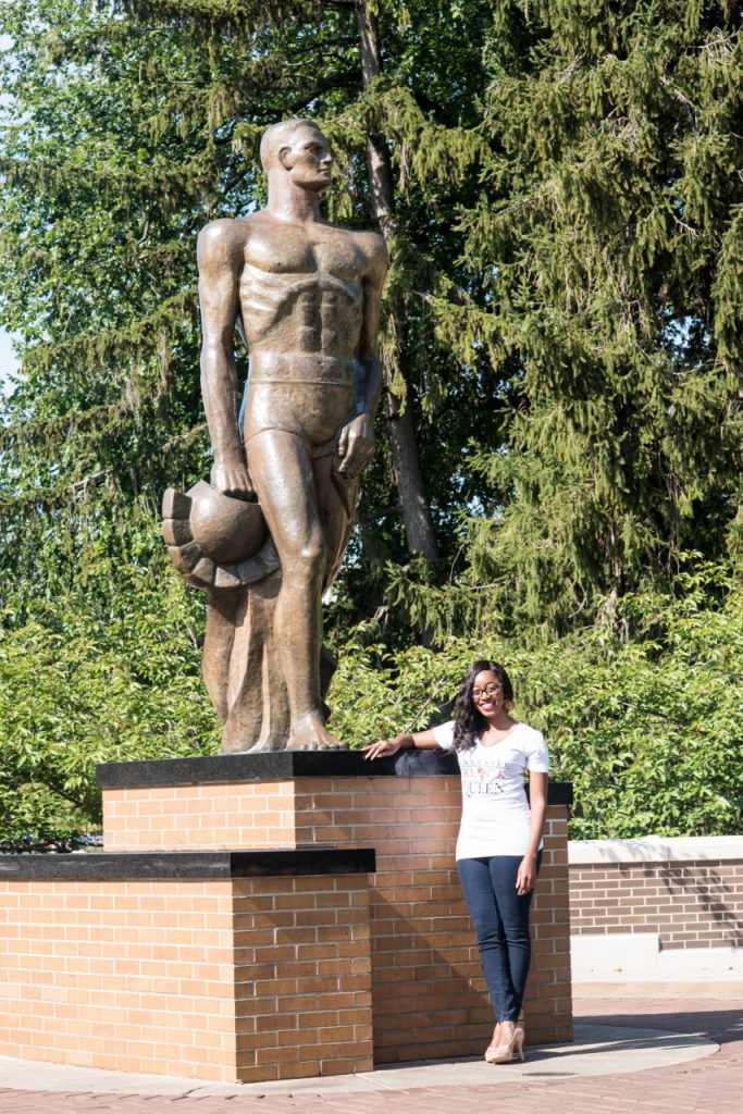 a woman in a t-shit, jeans, and glasses posing while leaning onto the Sparty statue on a sunny day