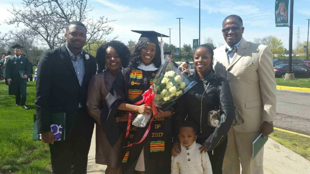 a woman in a cap and gown surrounded by five family members as they smile for a picture