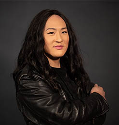 headshot of a woman with long, curly, black hair and wearing a leather jacket