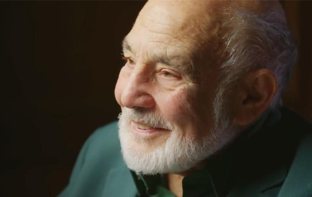 a man with a white beard wearing a green shirt smiling