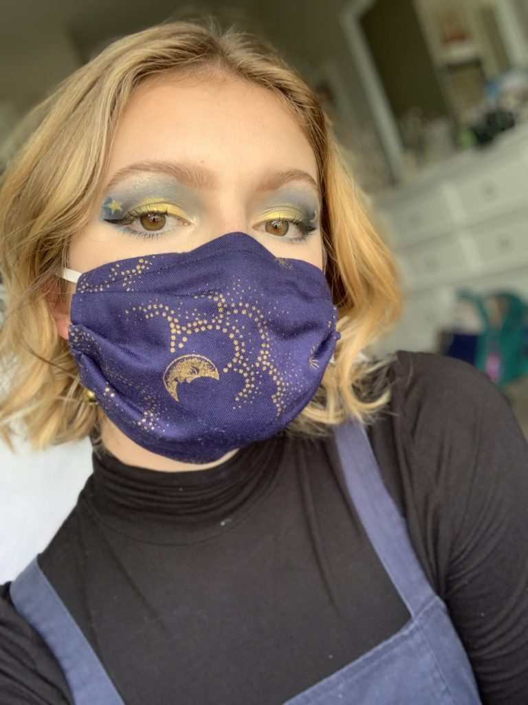 a girl with short hair wearing a purple mask and a black shirt