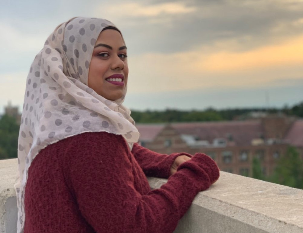 woman wearing a burgundy sweater and a headscarf looking out to a city
