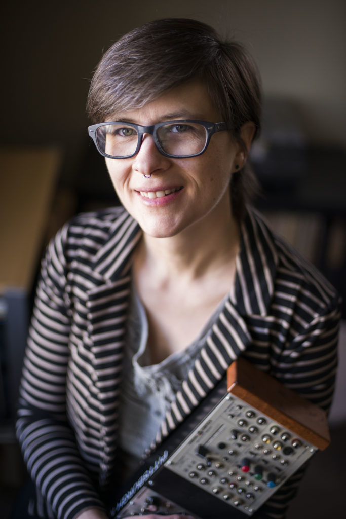 a woman with short hair wearing glasses and a striped jacket