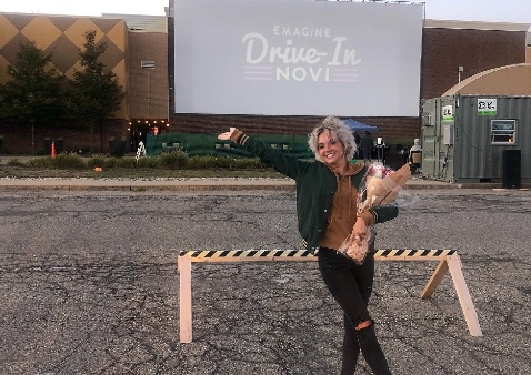 a girl in a green coat and black jeans standing in front of a drive in movie theatre