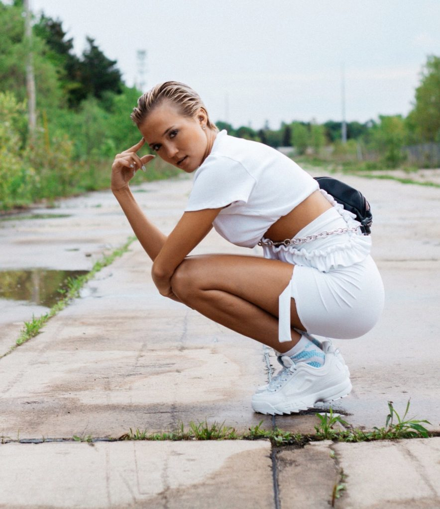 a girl with slicked back blonde hair wearing a white shirt and a white skirt