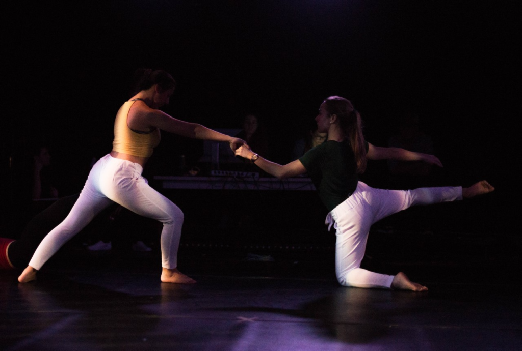 two woman in the middle of a dace with one on her feet with her hand extended to the other woman on her knee with one leg lifted up
