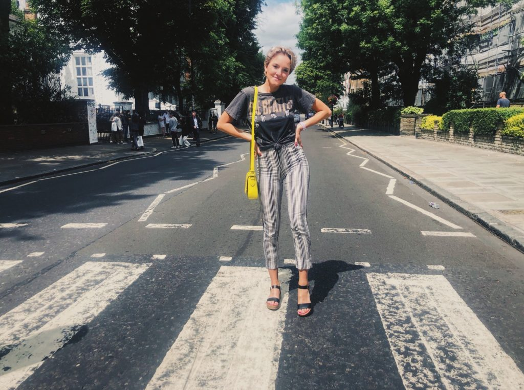 a girl in stripped pants and a Beatles shirt standing in the street in London