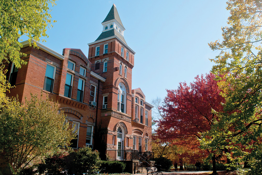 A brick building with a white steeple on a sunny day as the trees begin to change to fall colors.