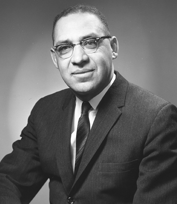 a black and white image of a man wearing glasses in a suit