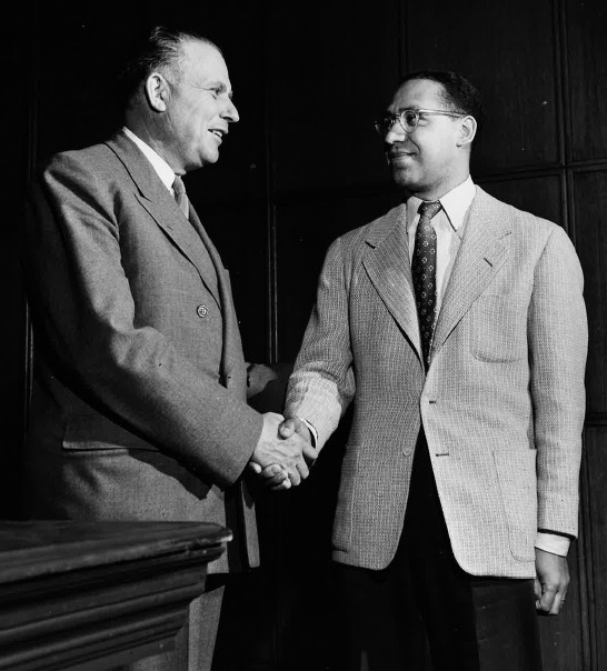 a black and white image of two men shaking hands
