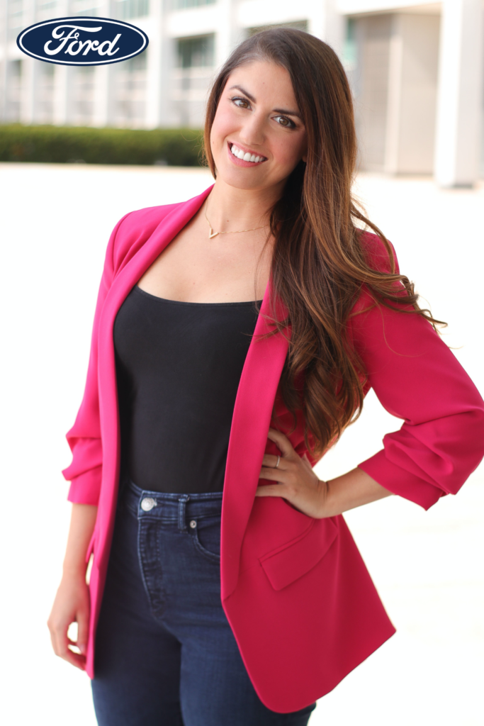woman wearing a pink jacket over a black shirt and blue jeans with her hand on her waist smiling at the camera with a Ford logo in the top left corner of the image