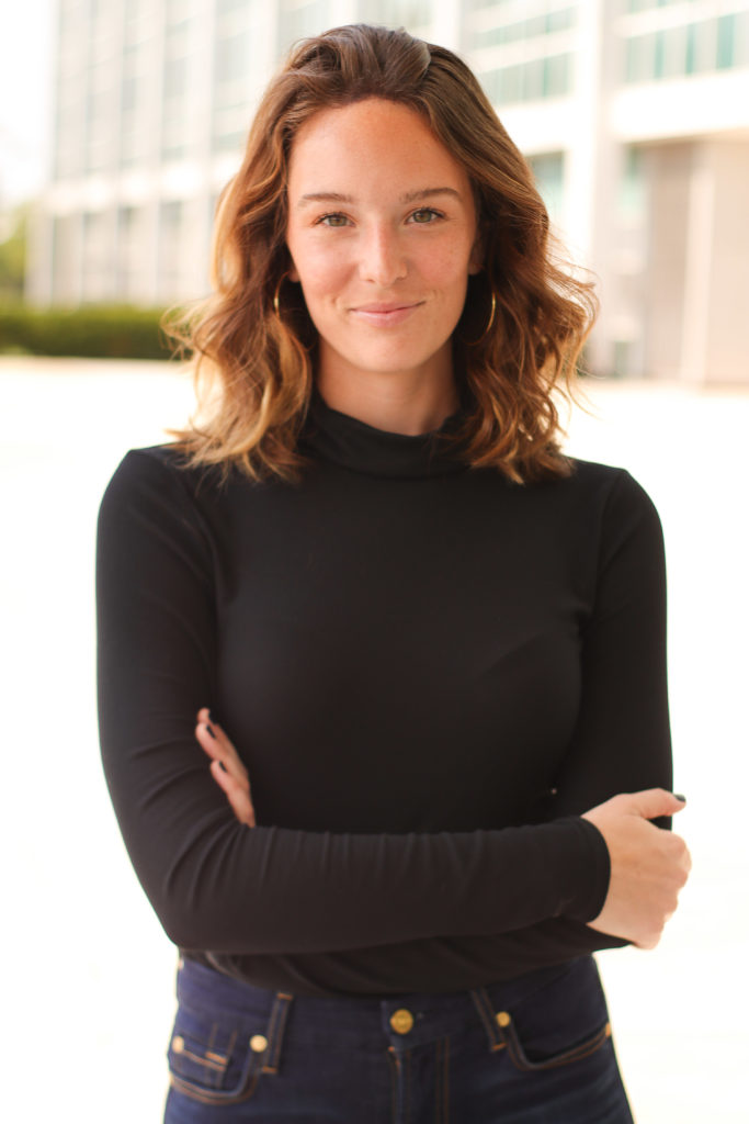 woman wearing a black long sleeved shirt with here alms crossed smiling at the camera