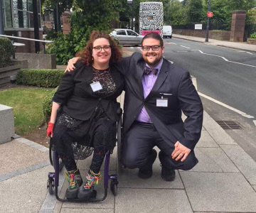 a woman with curly hair wearing a black dress and coat sitting in a wheel chair and a man in a dark grey suit with a purple shirt and tie, both wearing glasses