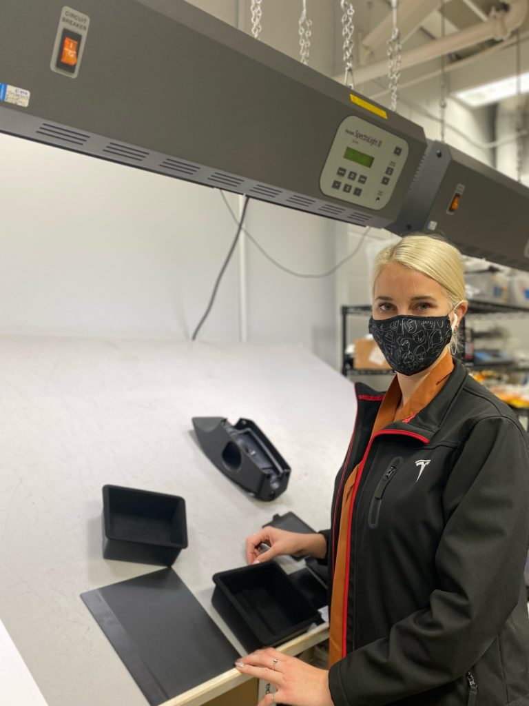 woman  with hair pulled back wearing a clack and white patterned mask, and black jacket standing next to some sort of technology