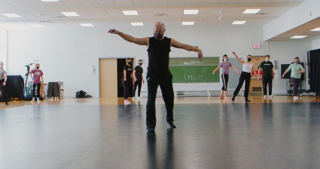man wearing a black outfit stnding in the middle of the room doing a dance move with his arms up in the air