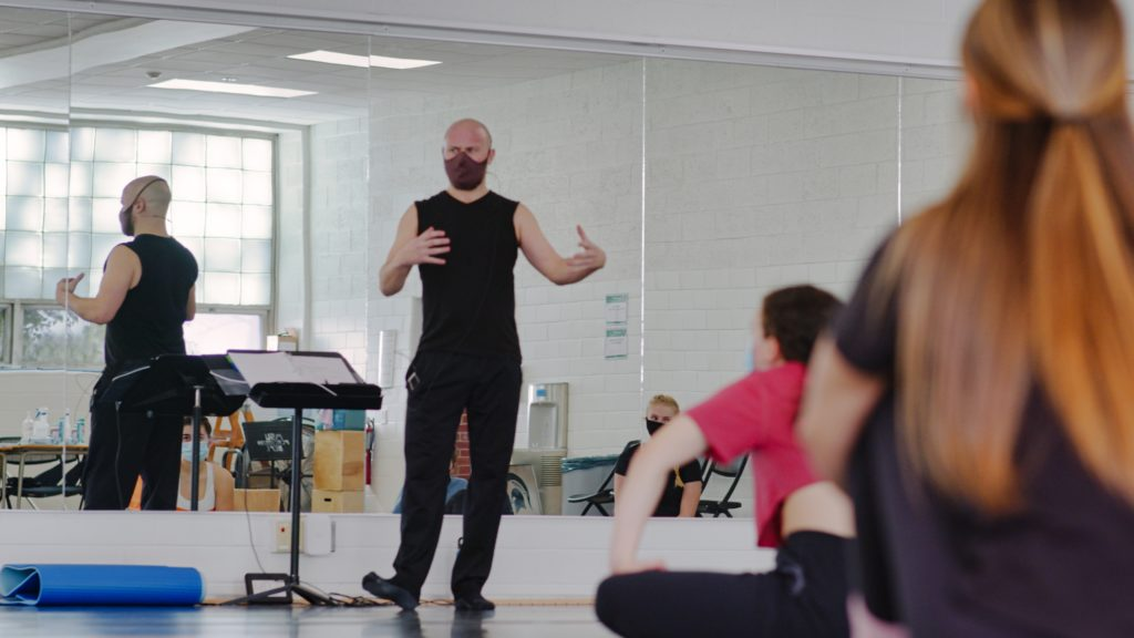 Man wearing a black outfit dtanding in front of a class in a room of mirrors