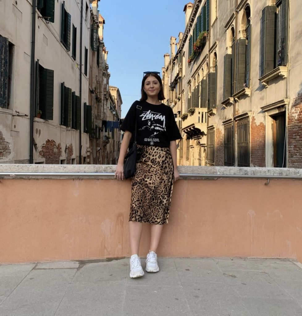 woman wearing a black graphic top with a long skirt and white sneakers standing in front tan buildings in the background