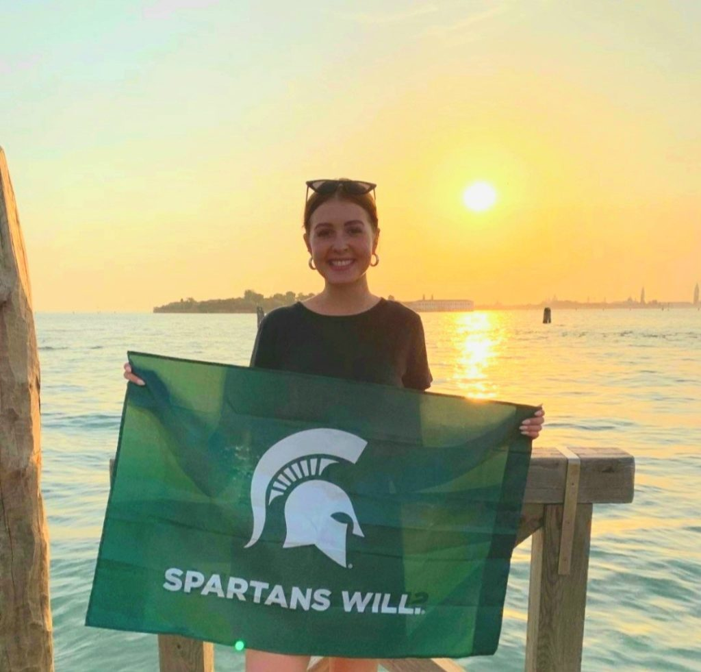 woman wearing a black top holding a Michigan State flag standing in front of a sunset above the water