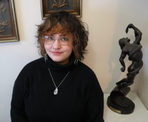 woman wearing long sleeve black shirt and a silver necklace wearing glasses