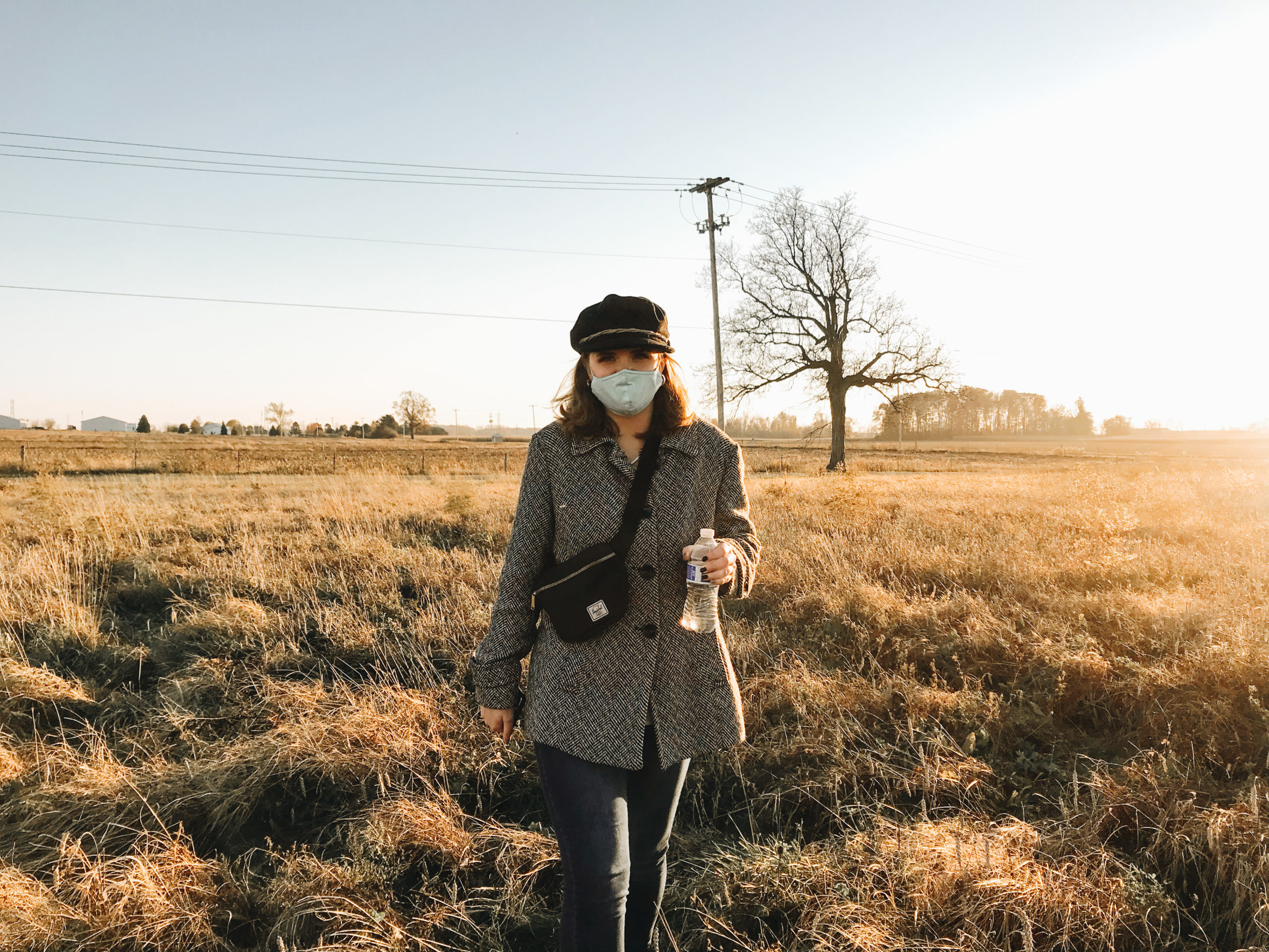 Photo of a woman wearing a gray jacket, black hat, black cross-body bag, and blue surgical mask is holding a plastic water bottle and standing in a field of brown grass.