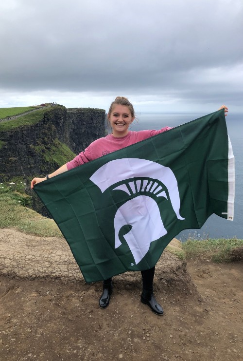 a girl on cliffs holding an MSU flag wearing a pink long sleeve, leggings, and rain boots
