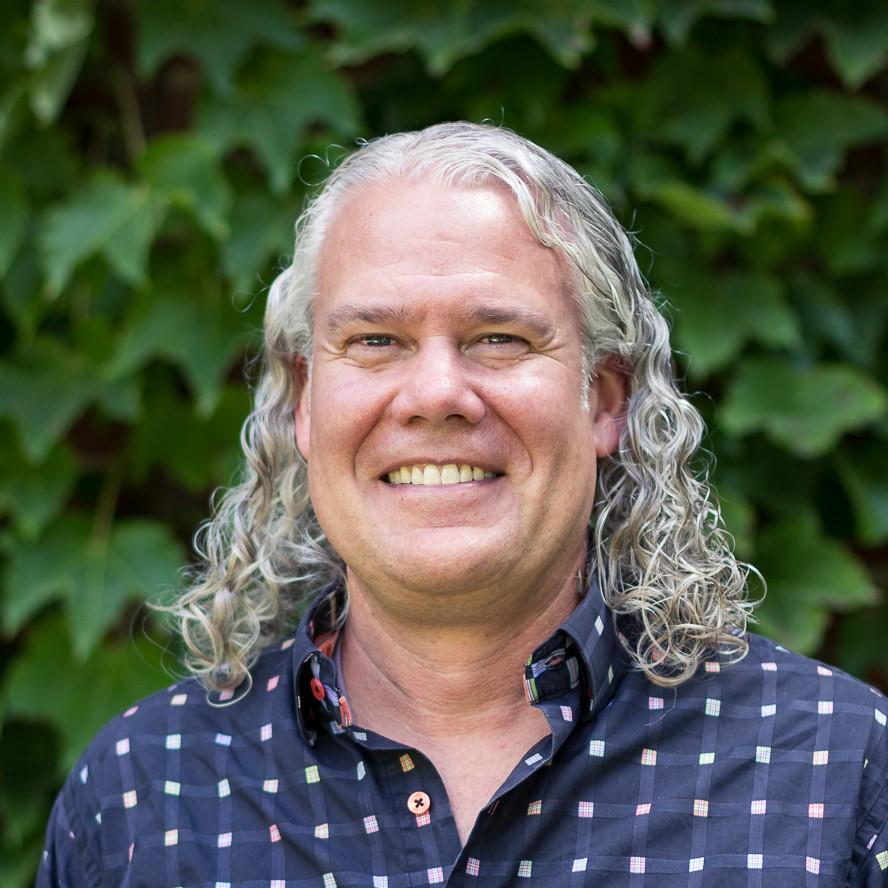headshot of a man with long white hair wearing a blue button down shirt