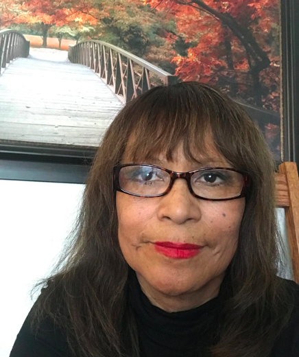 Photo of a woman with brown hair and bangs wearing tortoise