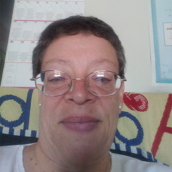 Photo of a woman with wire framed circular glasses and short brown hair