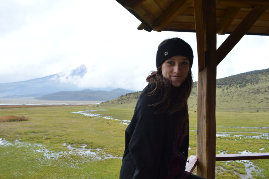 Photo of a woman with brown hair wearing a black headband and black coat. In the background is an expanse of green wetlands and a mountain.