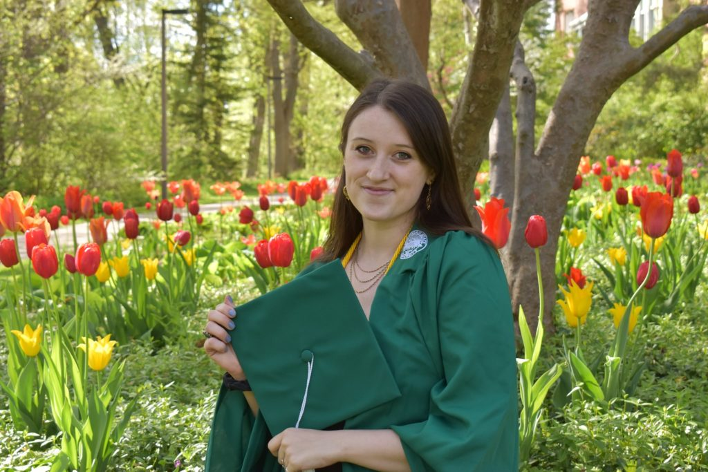 Photo of a woman with brown hair wearing a green graduation gown and holding a graduation cap in front of her chest. In the background are red and yellow tulips.
