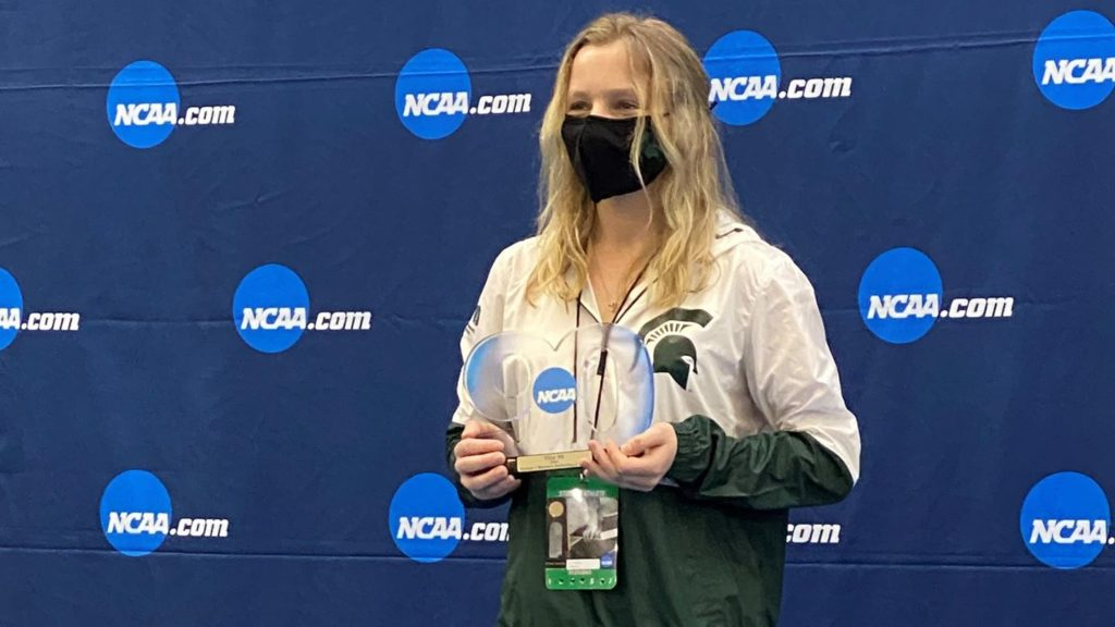 """Photo of a woman with blonde hair holding an award made of glass shaped in the number """"90"""". She is wearing a black face mask and a white and green windbreaker. Behind her is a blue backdrop with light blue circles and the acronym, NCAA.com"""