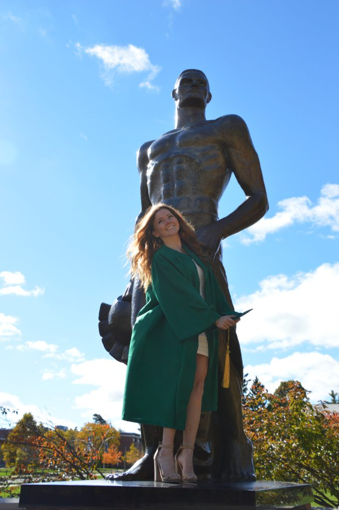 Woman with red hair wearing a green graduation gown standing in front of the Spartan Statue at MSU