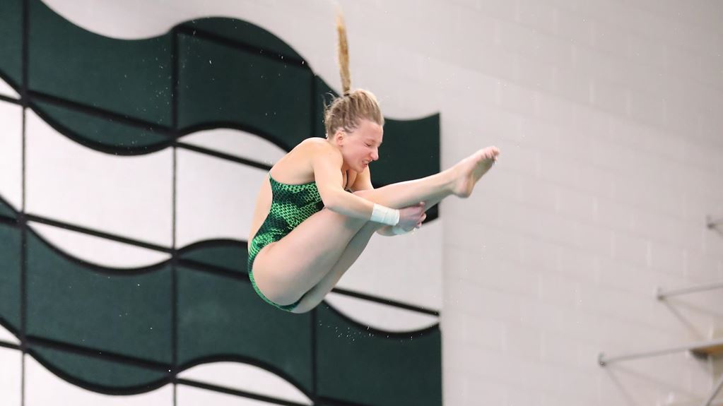 Photo of a woman with blonde hair in a ponytail diving. Her arms are wrapped around her outstretched legs and she is wearing a green one-piece swimsuit