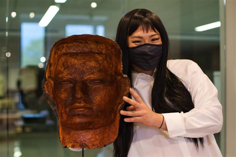Photo of a person standing next to a metal casting of a head. They have long black hair and are wearing a face mask and white dress shirt.