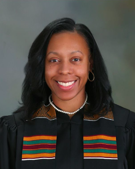 Photo of a woman with shoulder-length black hair wearing a black judge gown