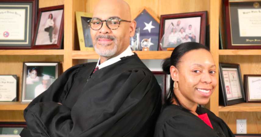 Photo of a man (left) and woman (right) both wearing judge gowns and standing back to back. In the background are bookshelves with photo frames on them.