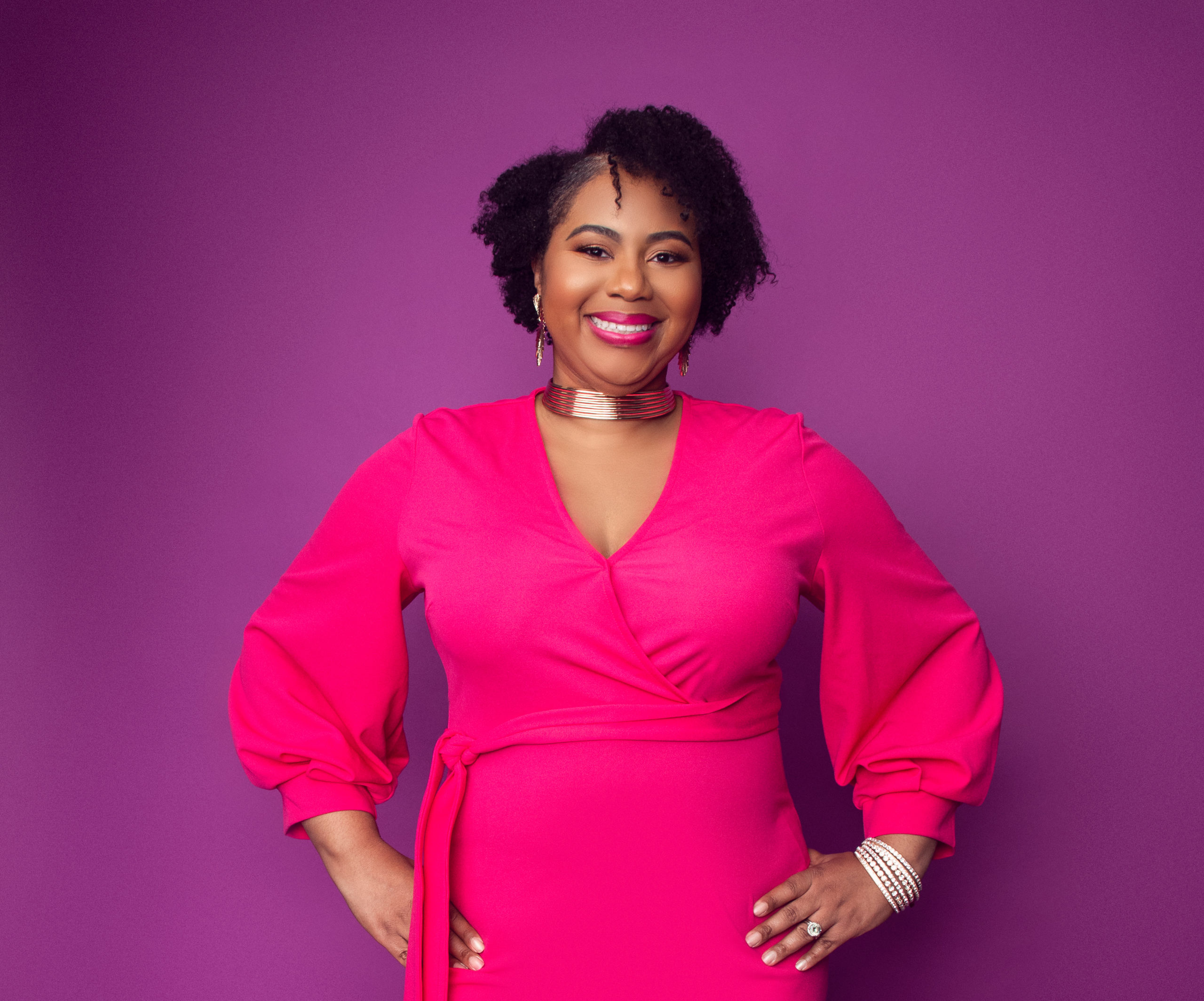 Woman with black hair is smiling and wearing a pink dress. Her hands are on her hips.