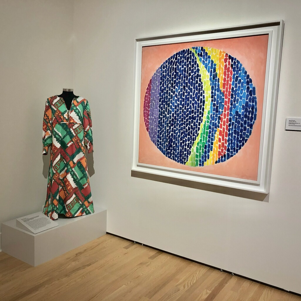 Exhibit of a red, green, and orange dress next to a framed painting of a multicolor circle.