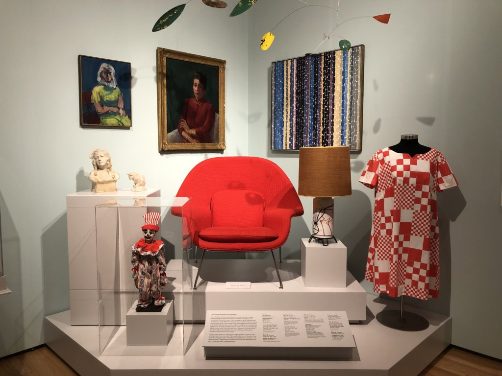 Photo of an exhibit showing a red chair in the center, a red and white dress to the right, and other artifacts like paintings and sculptures
