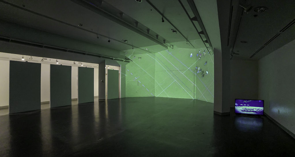 Photo of an exhibit showing one wall with a projected image and a tv in the corner.