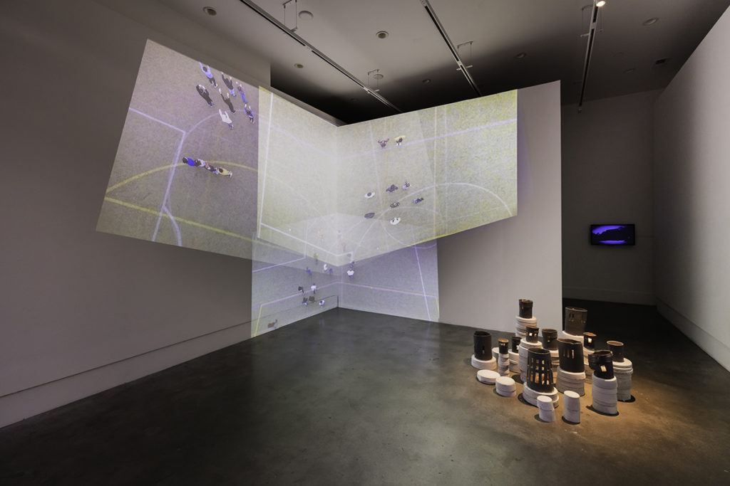 Photo of an art exhibit. There is a screen showing a soccer game and ceramics on the floor.